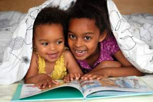 cute kids reading under a blanket