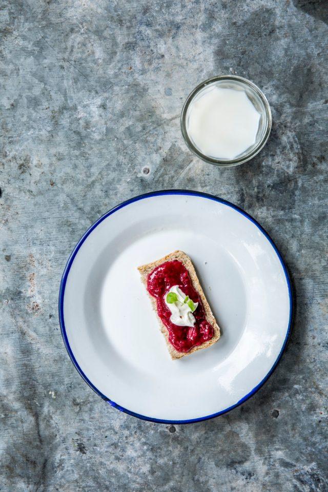 En halv skive med syltetøy og rømme, på en tallerken med kontrastfarget kant og et glass melk