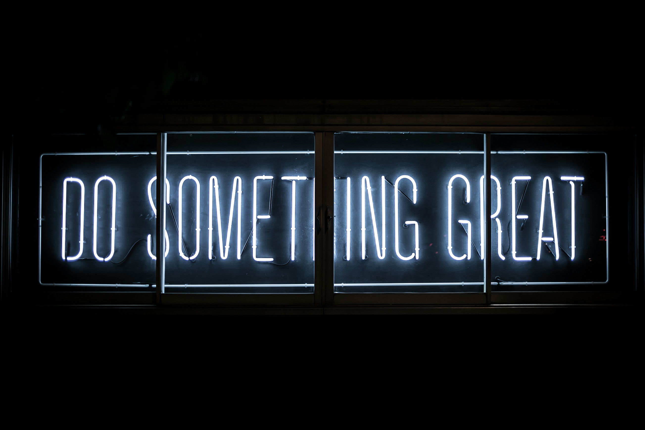 "Neon sign reading, ""do something great."""