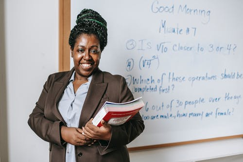 A teacher holding books, standing in front of a white board