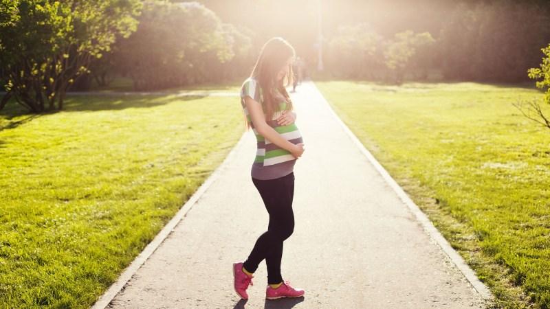 kobieta w ciąży stoi na drodze, trzyma się za brzuch, oświetla ją słońce, za nią jest park