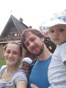 rodzina mama tata syn i córka, córka na rękach u taty z prawej a synek w chuście u mamy z lewej