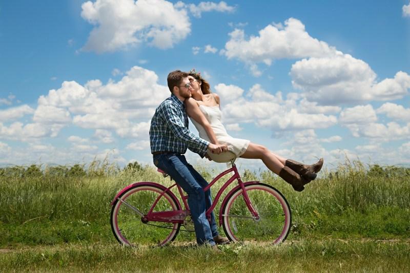 zakochana para jedzie na rowerze po łące, on prowadzi, ona siedzi na kierownicy