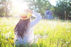kobieta w kapeluszu siedzi na łące i wpatruje się w świecące słońce