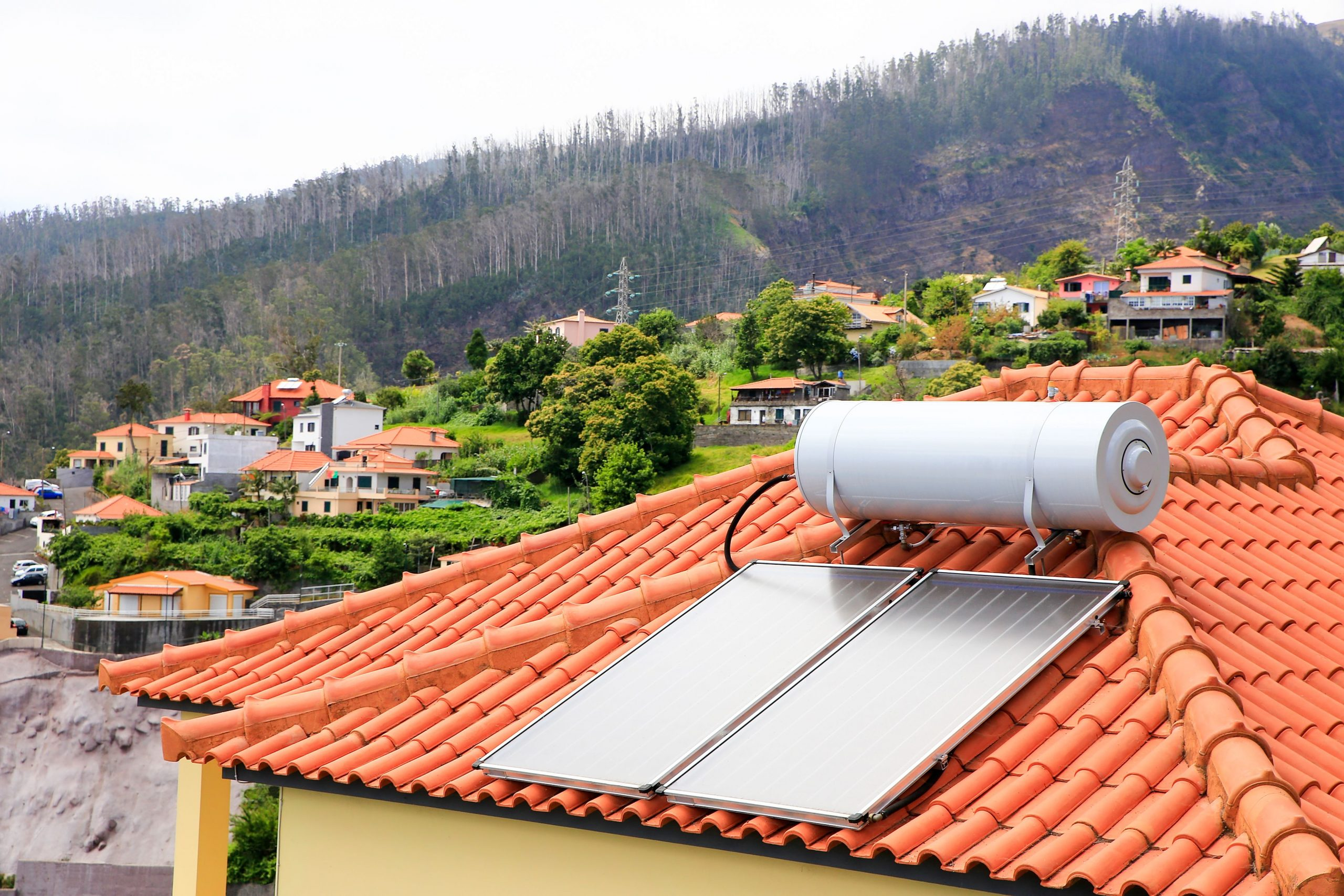 Water boiler with solar panels on roof of house