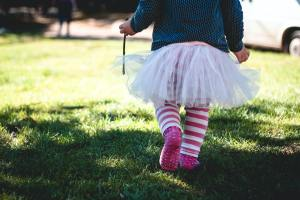 small child in galoshes and a tutu