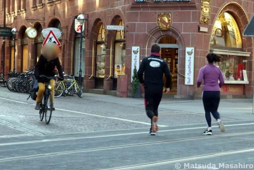中心市街地を走る自転車とジョギングする人(3月24日撮影)