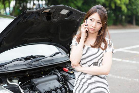 車のトラブルで電話する女性