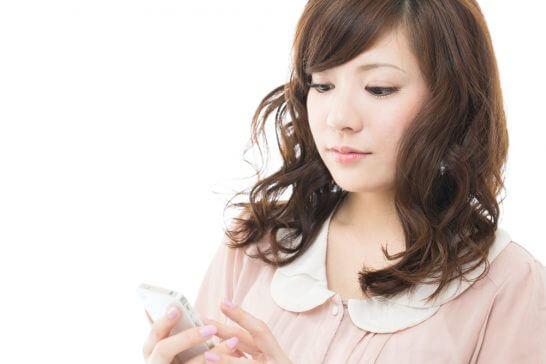 スマートフォンを見て考える女性