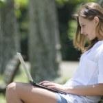 公園でノートPCを操作する女性