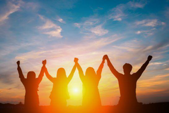 夕陽を浴びながら手を合わせてバンザイする仲間たち