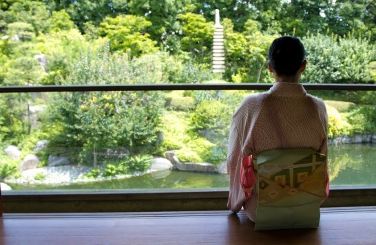 庭園を見る着物の女性