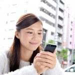 スマートフォンを見る笑顔の女性