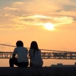 夕日にブリッジの前で座る男女