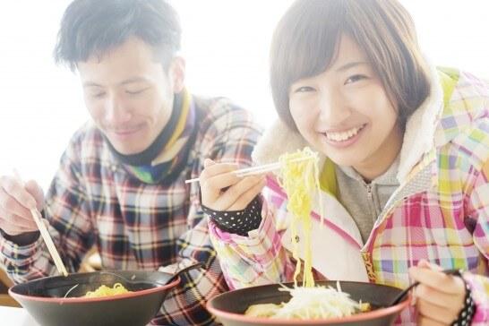 スキー場で食事する男女