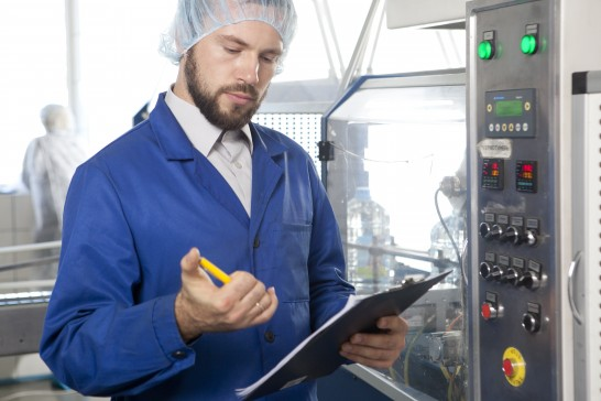 工場内で機械の調子を見守る男性