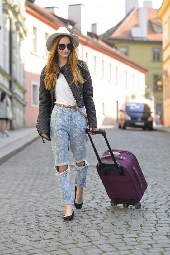 キャリーバッグを持って歩く女性