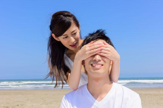 ビーチで男性の目を隠す女性