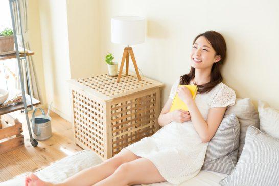 住宅で本を抱える笑顔の女性