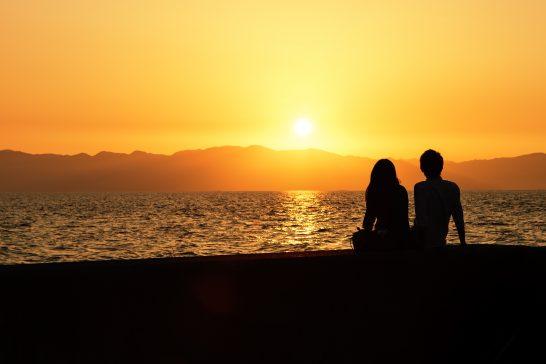 海沿いの夕焼けとカップル