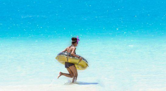 シュノーケリングセットと浮き輪を持って駆け出す女性