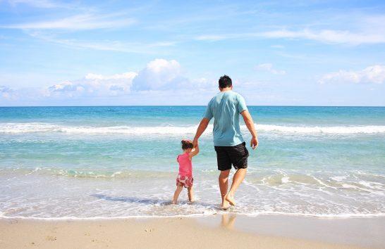 海辺で水遊びする親子