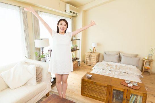 住宅の中で手を広げる笑顔の女性