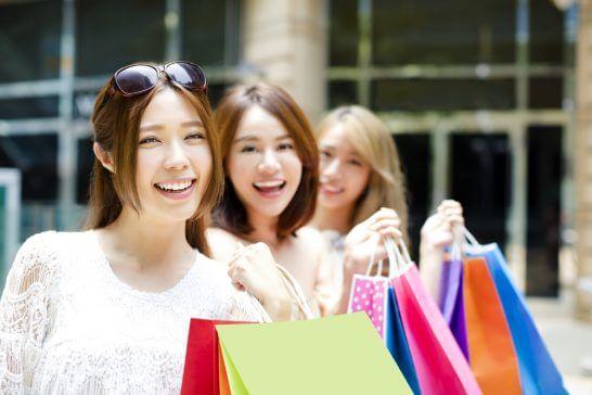 クレジットカードを見せるショッピング中の3人の女性