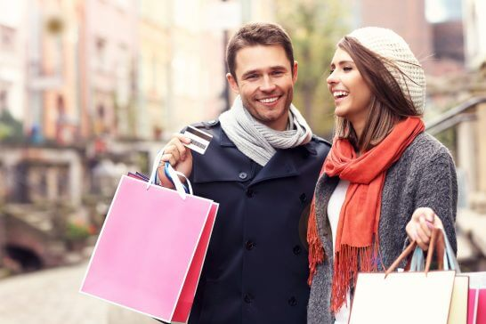カードを見せるショッピング中の男女