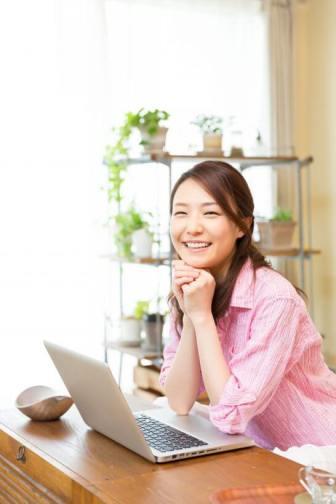 ノート・パソコンと笑顔の女性
