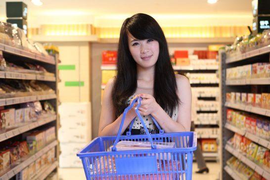 スーパーでかごを持つ女性