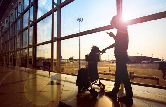 空港で荷物を持ちながらスマホをみる人