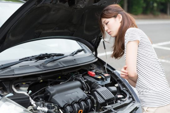 自動車が故障して困った表情の女性