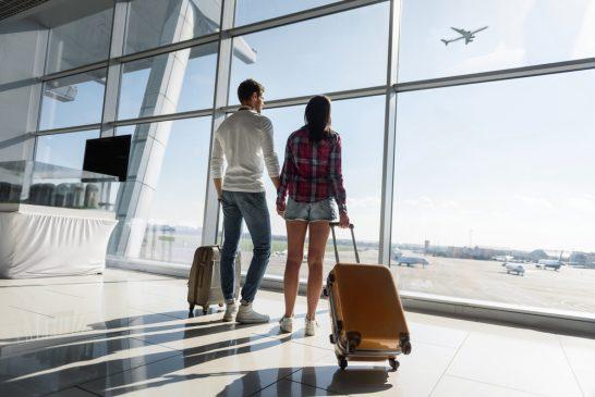 空港で外を眺める男女