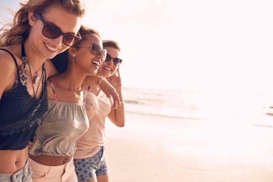 海岸で遊ぶ笑顔の女性
