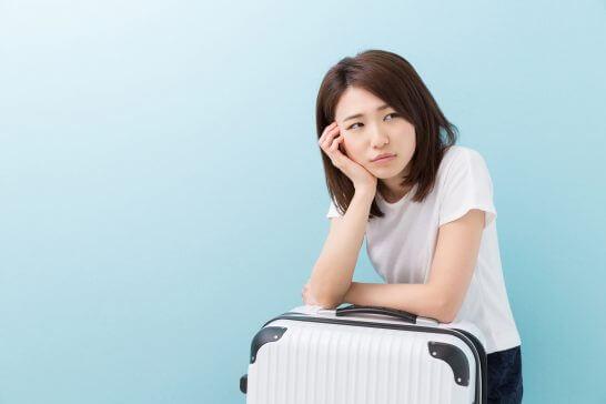 スーツケースで頬杖をつく困った表情の女性