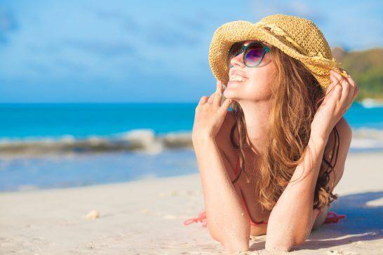 ビーチの砂浜で横たわる笑顔の女性