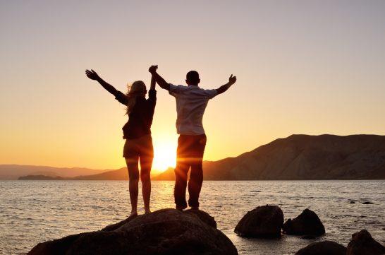 海辺でバンザーイと手を広げる男女