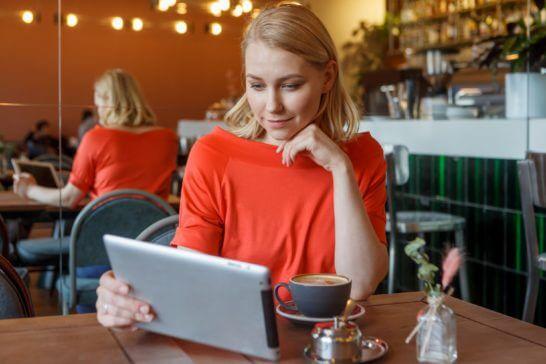 カフェでタブレットを見る女性