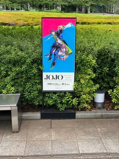 国立新美術館の庭のジョジョの奇妙な冒険の原画展の看板