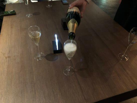 ラグジュアリーカードの優待特典のシャンパンを注ぐシーン