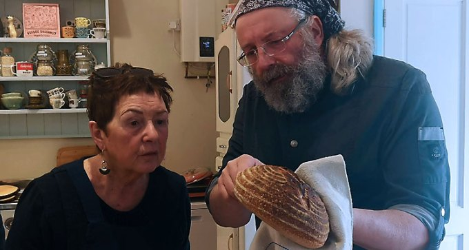 Carol-Ann and Klaus examine a freshly-baked sourdough loaf
