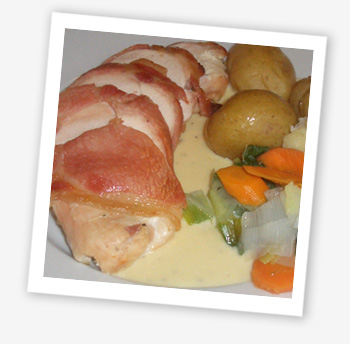 Supreme of chicken stuffed with a cheese, ham and herb filling wrapped in bacon with a creamy garlic sauce