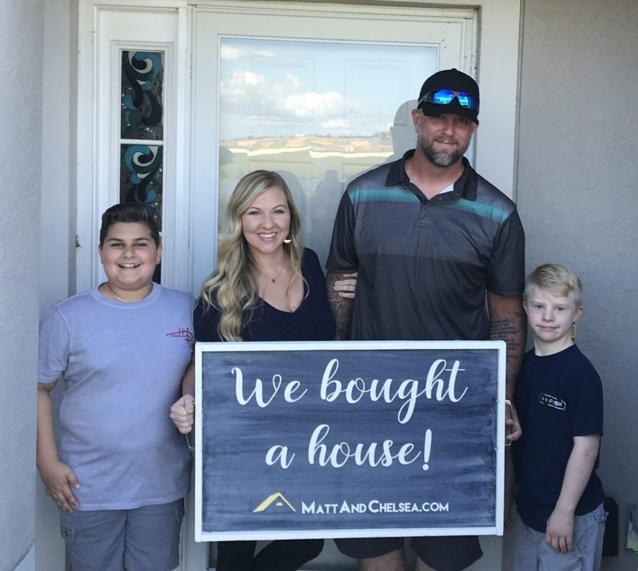 "The Burnsed family - husband, wife, and two boys - stand in front of the front door of the home they bought holding the sign, ""We bought a house!"""