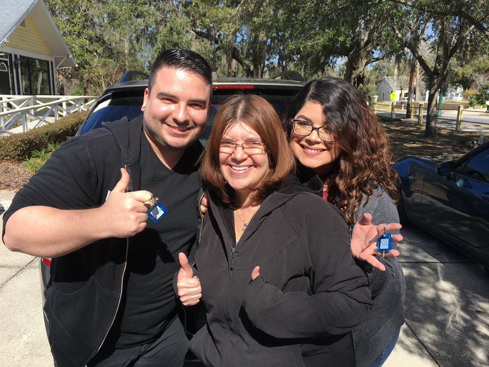 Kris, Maritza, and Laura smile while holding keys to the home they just bought.