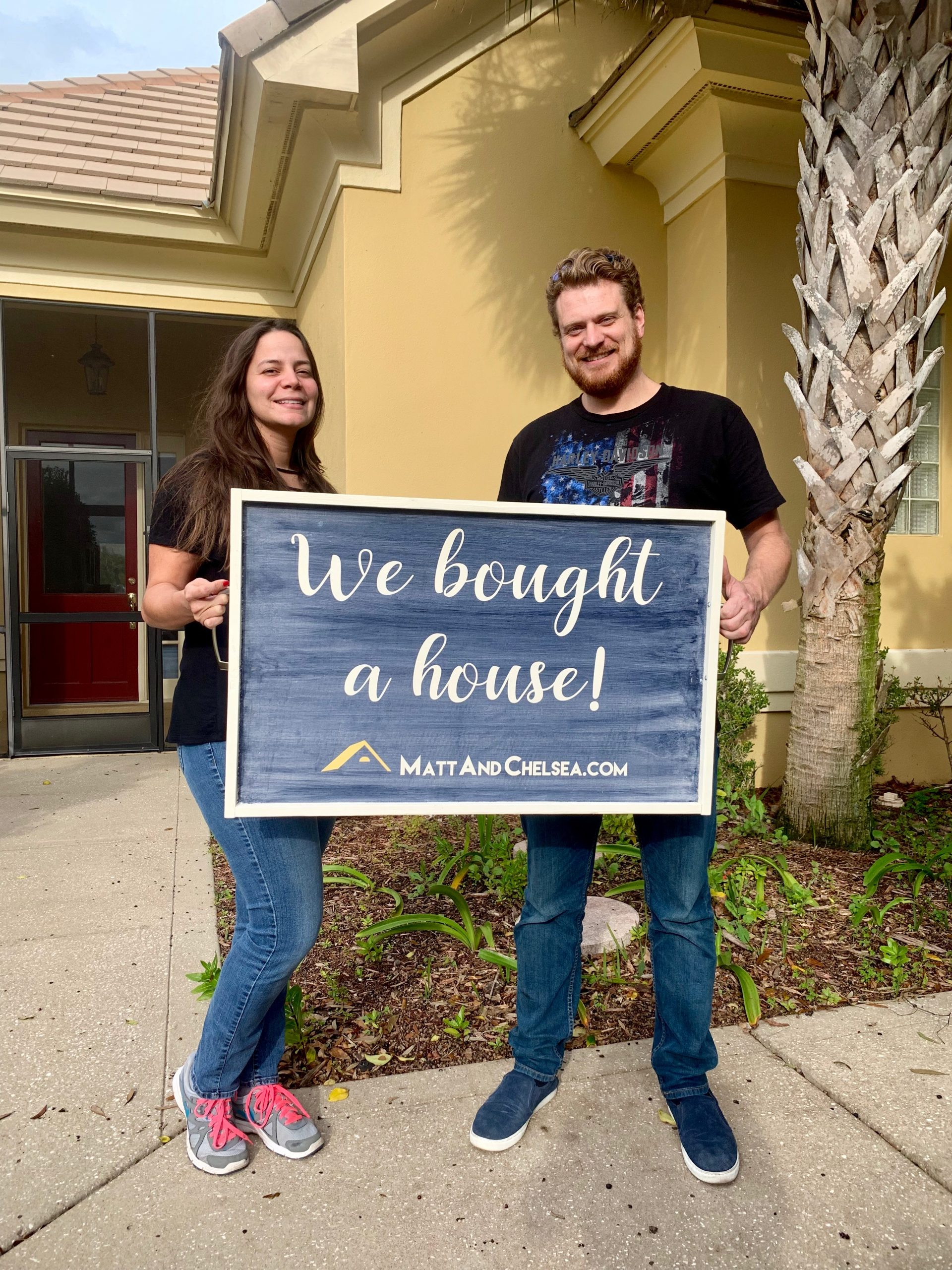 """Photo of clients Ron and Carmen holding a """"We bought a house!"""" sign in front of the home they purchased."""