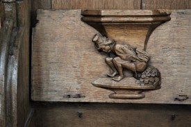 Old Dutch saying depicted on a misericord in Oude Kerk: You can't poop money.