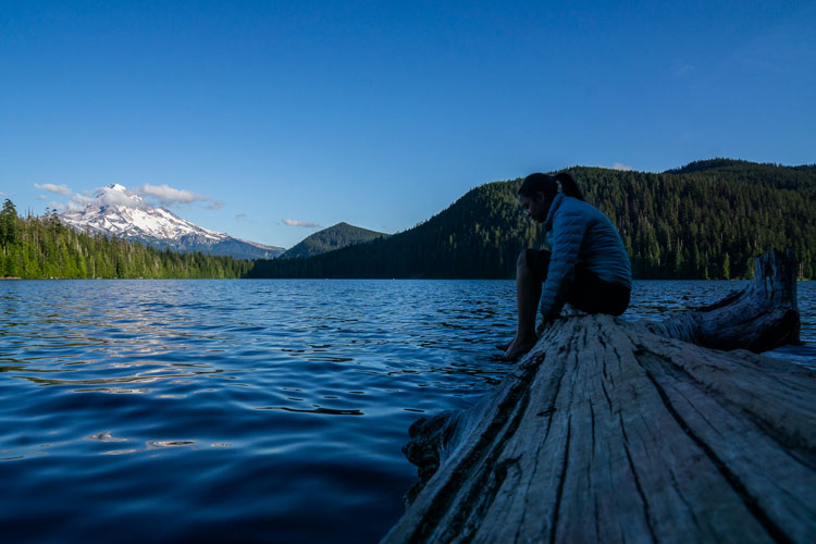Woman sitting on log looking into Lost Lake, Oregon, with Mt Hood in the distance.