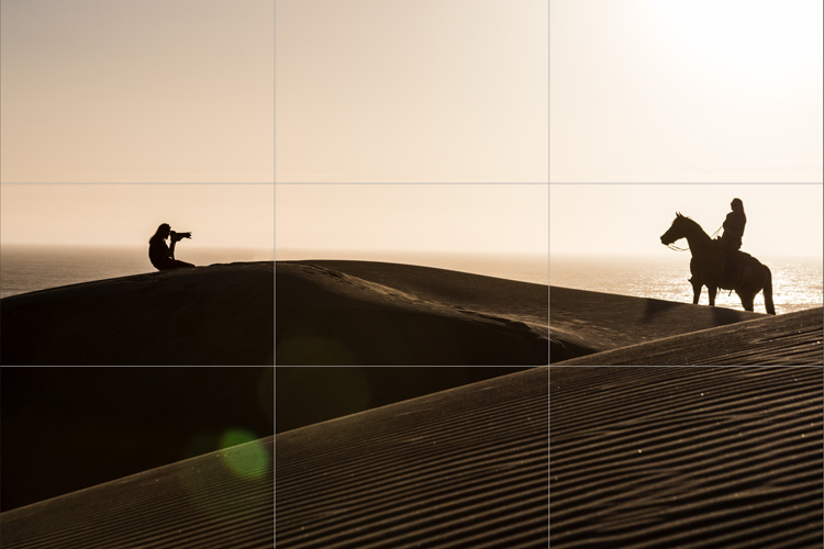 Silhouettes of a photographer capturing a portrait of a woman on horseback at the Oceano Sand Dunes.