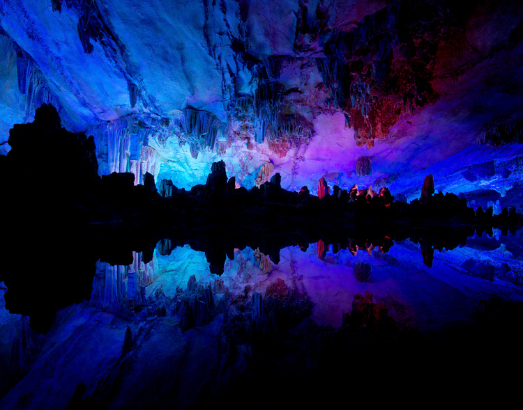View inside the famous Reed Flute Cave in Guilin, China. Stalactites and stalagmites reflected in a a pool of water.